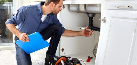 plumber assessing pipes under the sink