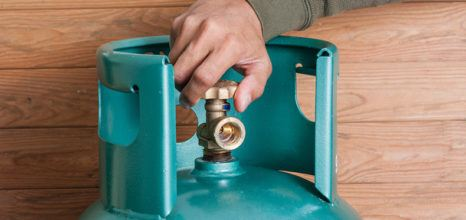 hand turning on blue-green gas cannister