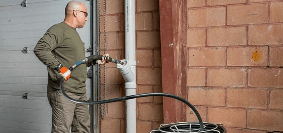 Man using robot cutter to clean pipes