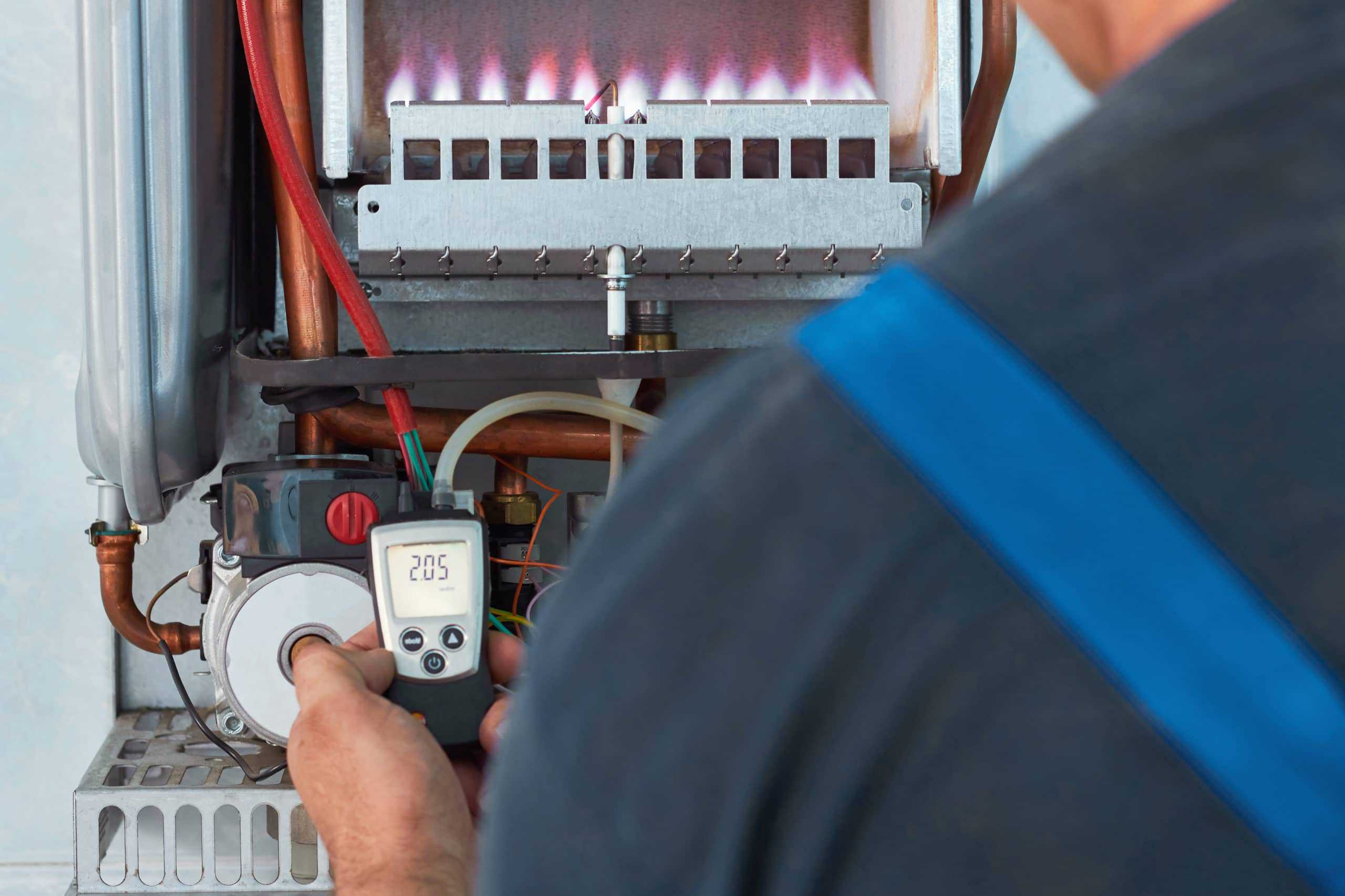 commercial plumbing using a tool to check a hot water system