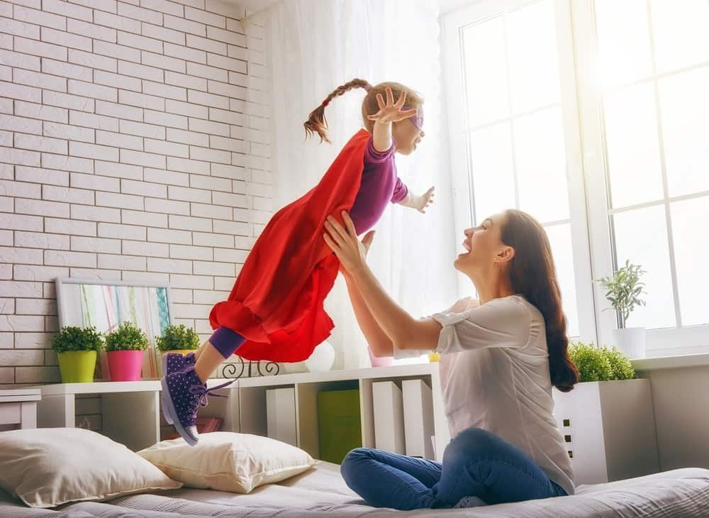 Mother holding up daughter dressed as super hero in bedroom